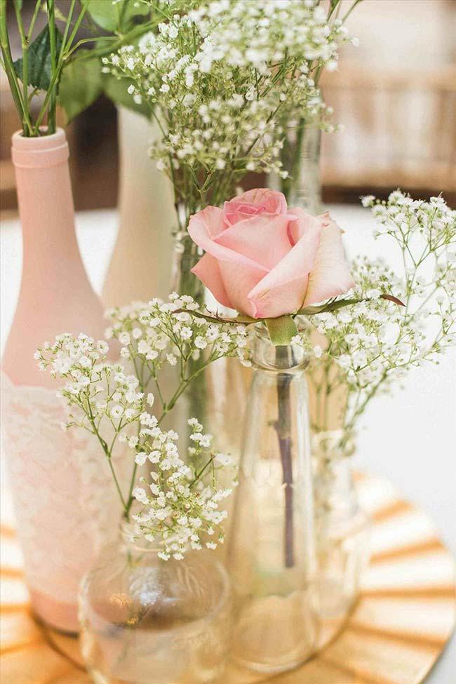 Gispsofila e rosas em vasinhos solitários compõe a decoração desse casamento