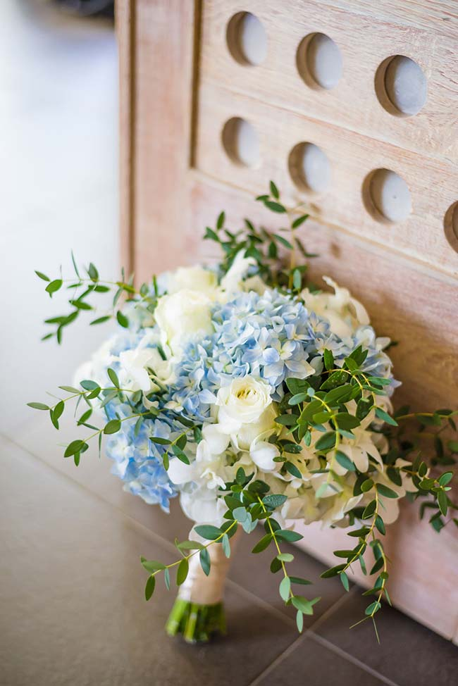 Hortênsias azuis e rosas brancas formam esse buquê de noiva