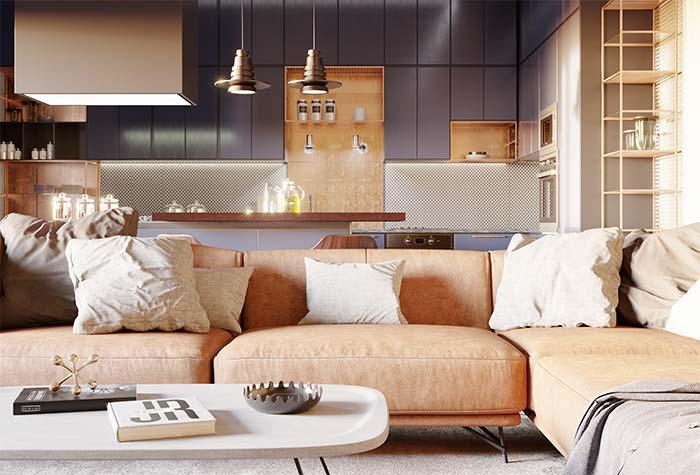 Já nesse ambiente integrado, o tom caramelo do sofá se repete nos armários da cozinha