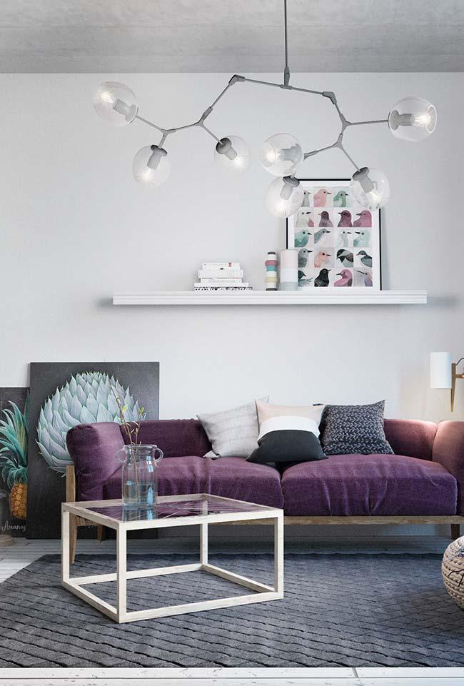 Branco e cinza na base da decoração, o roxo entra no sofá trazendo personalidade para a sala