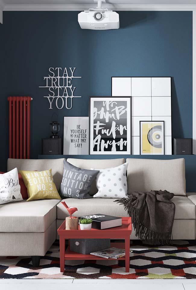 Sala moderna apostou na combinação entre azul fechado e o vermelho
