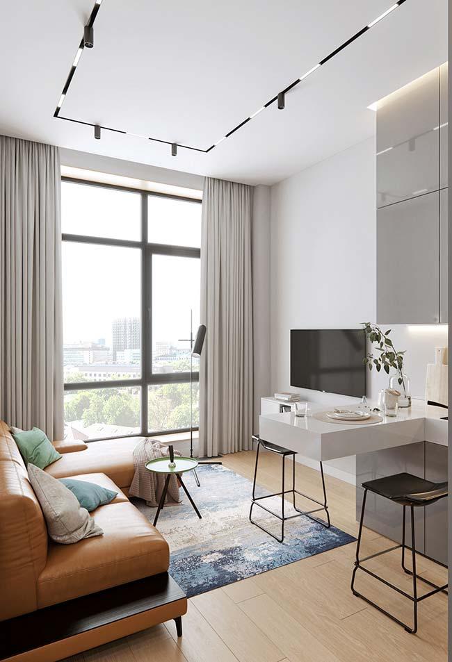 A decoração neutra e moderna dessa sala apostou em um clássico sofá de couro na cor caramelo
