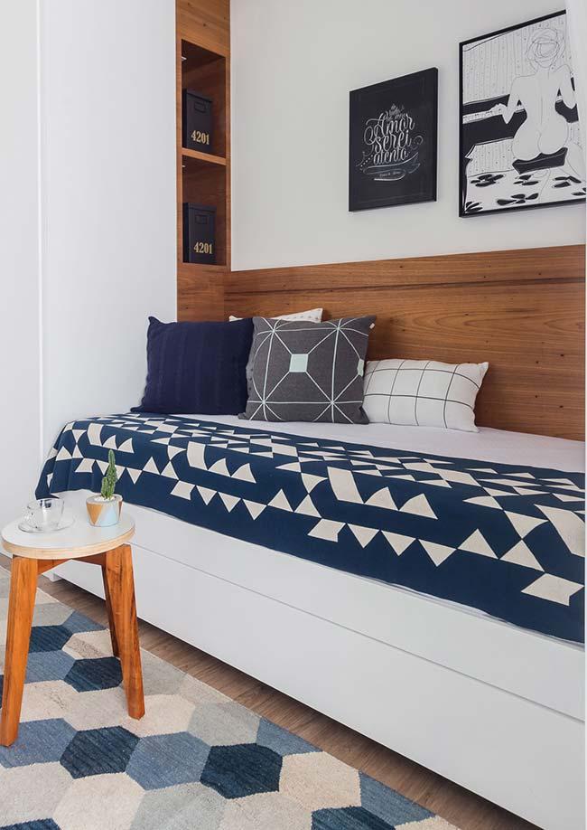 Nesse quarto de solteiro, a opção foi usar o mesmo material da cabeceira da cama para o nicho