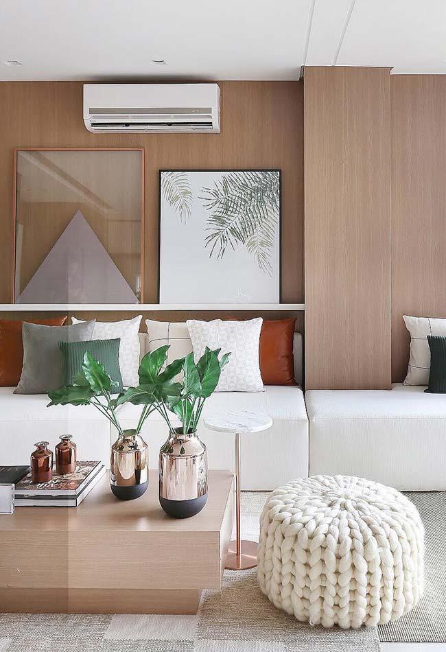Dois quadros apoiados sobre a prateleira acima do sofá