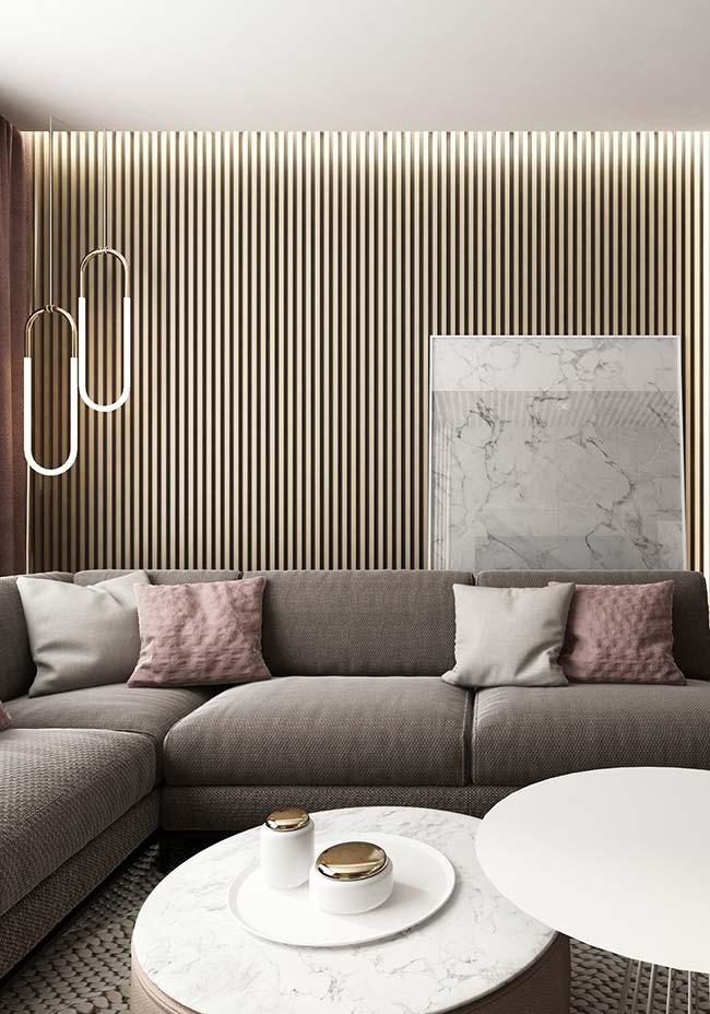 Sobre o revestimento de madeira, o quadro que lembra textura de mármore foi apoiado no chão e se revela atrás do sofá