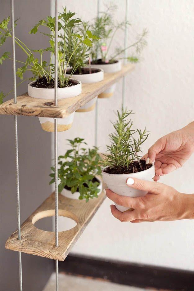 Jardim vertical suspenso de pallet; faça uma abertura nos pallets para encaixar os vasos