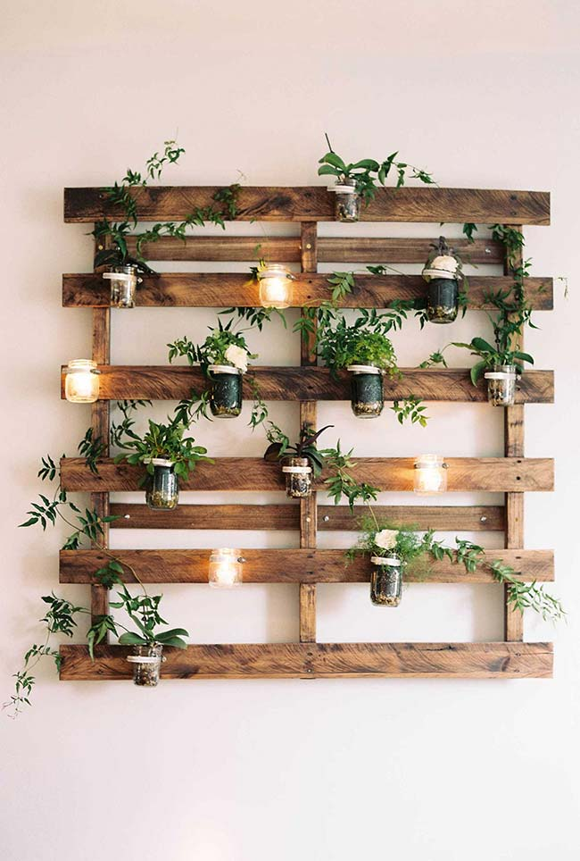 Decore o jardim vertical de pallets com velas em copos e ramos verdes