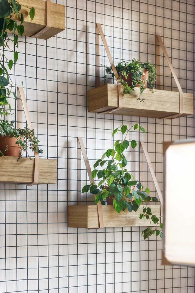 Nesse jardim vertical, os suportes de pallet foram suspensos na parede com a ajuda de cintas de couro