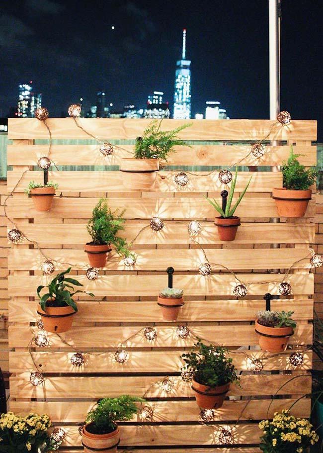 Esse jardim de pallets da área externa ficou mais bonito e funcional com o uso de um varal de lâmpadas
