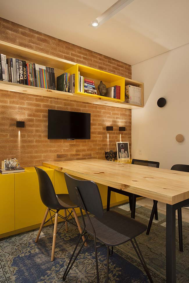 Móvel laqueado amarelo em contraste com a madeira crua da mesa e dos nichos