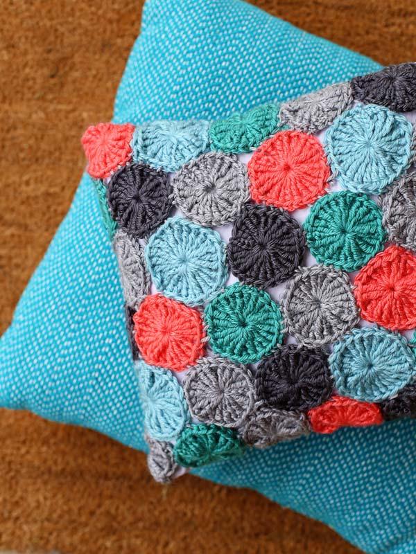 Capa de almofada feita com fuxicos coloridos de crochê
