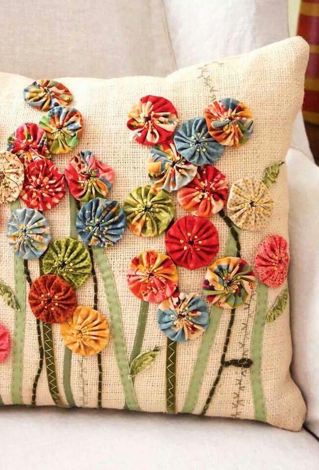 Nessa capa de almofada, os fuxicos viraram flores de um jardim