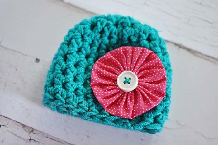 Para contrastar o azul da touca de lã, um fuxico vermelho