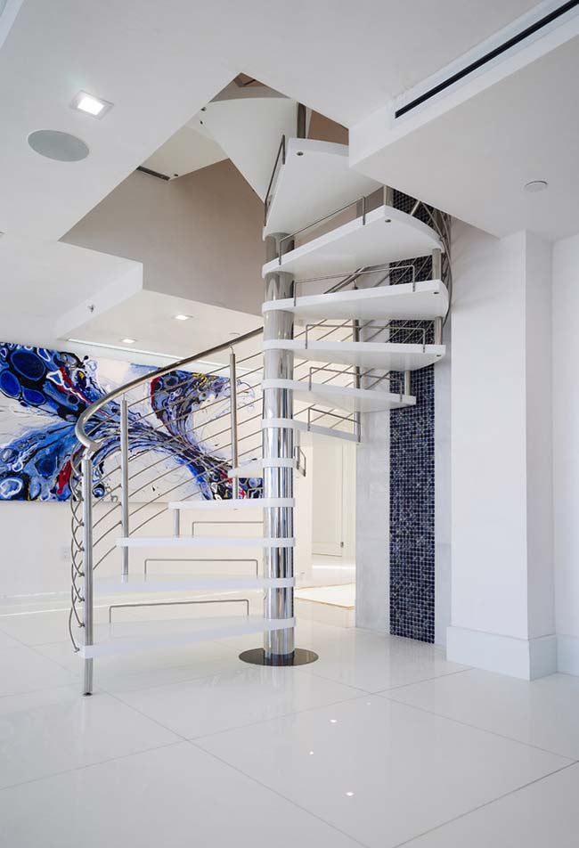 Numa decoração mais aberta e tecnológica, esta escada espiral mistura o aço inox e a pedra branca