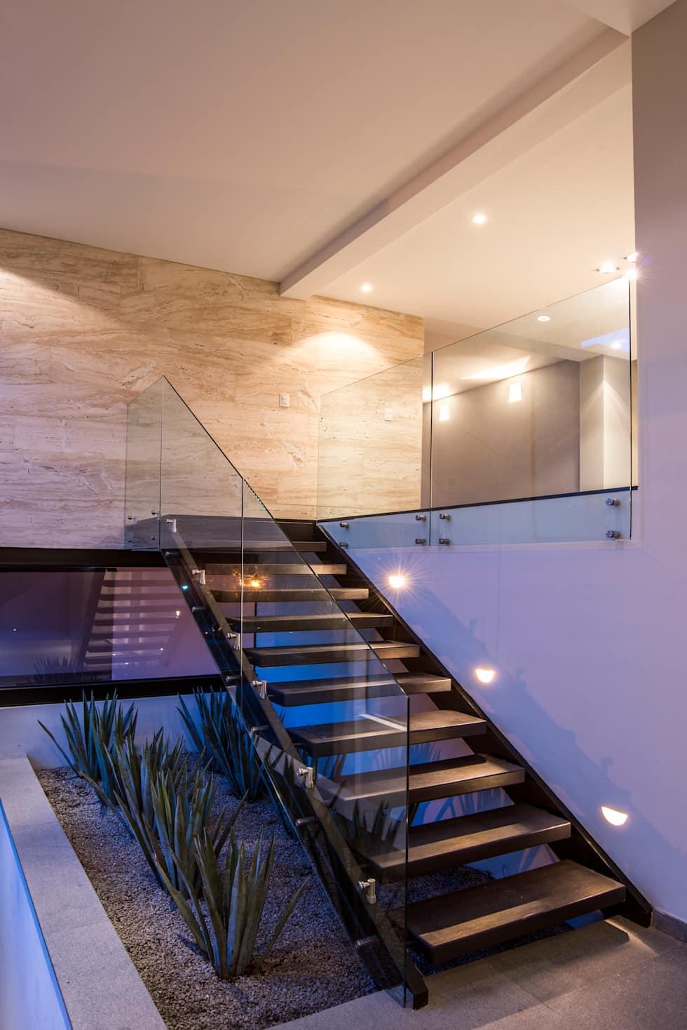 Elegância e sofisticação da escada de vidro contrastada pelo jardim de visual árido feito de pedras e espadas de são jorge