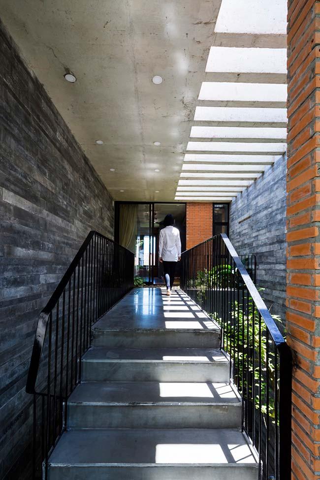 Escada de concreto que dá acesso ao interior da casa é seguida por folhagens em sua lateral