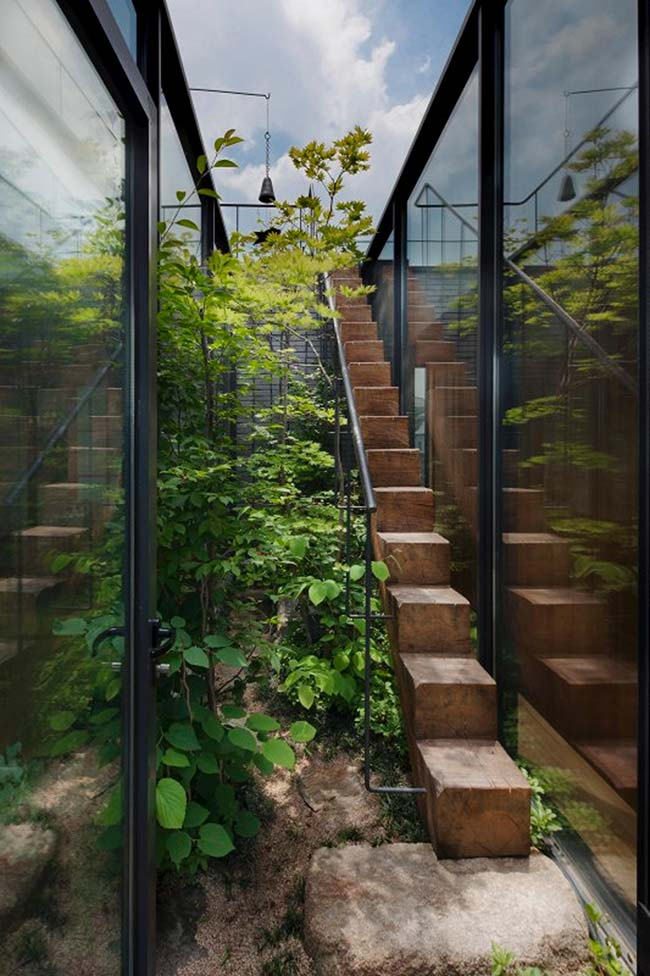 Essa escada externa parece competir por espaço com o jardim, ficando comprimida no cantinho