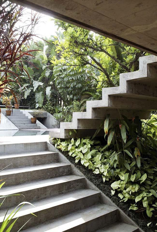 O jardim embaixo da escada externa se destaca pela presença dos singonios e da grama preta