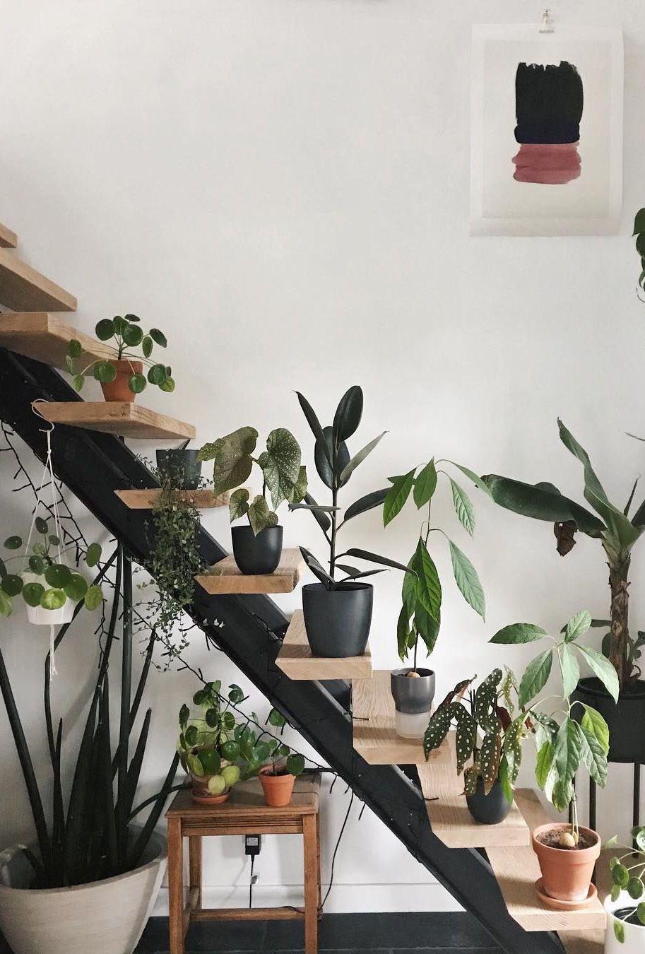 Aqui, o jardim embaixo da escada é formado por vasos e se estende por toda a extensão da escada