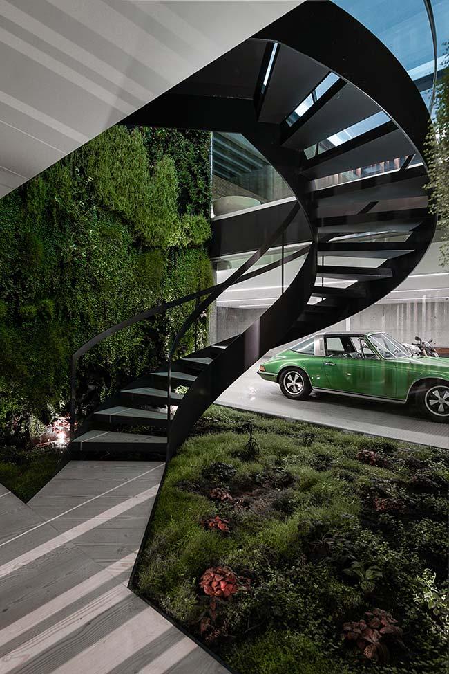 Escada caracol de design diferenciado foi cercada de plantas por todos os lados