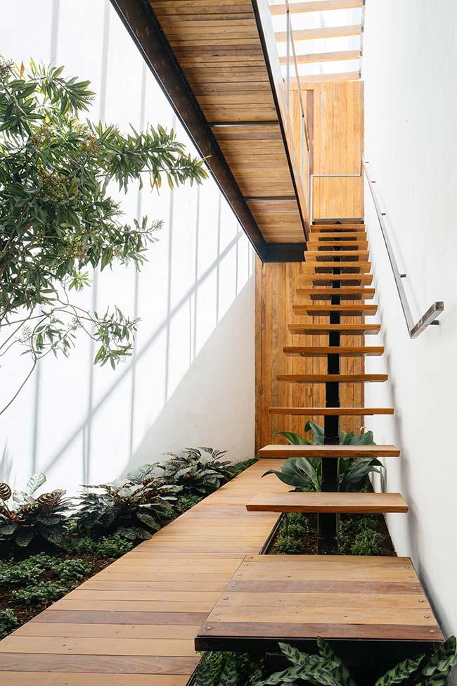 Um jardim junto a uma escada de madeira traz conforto e aconchego extra para a casa
