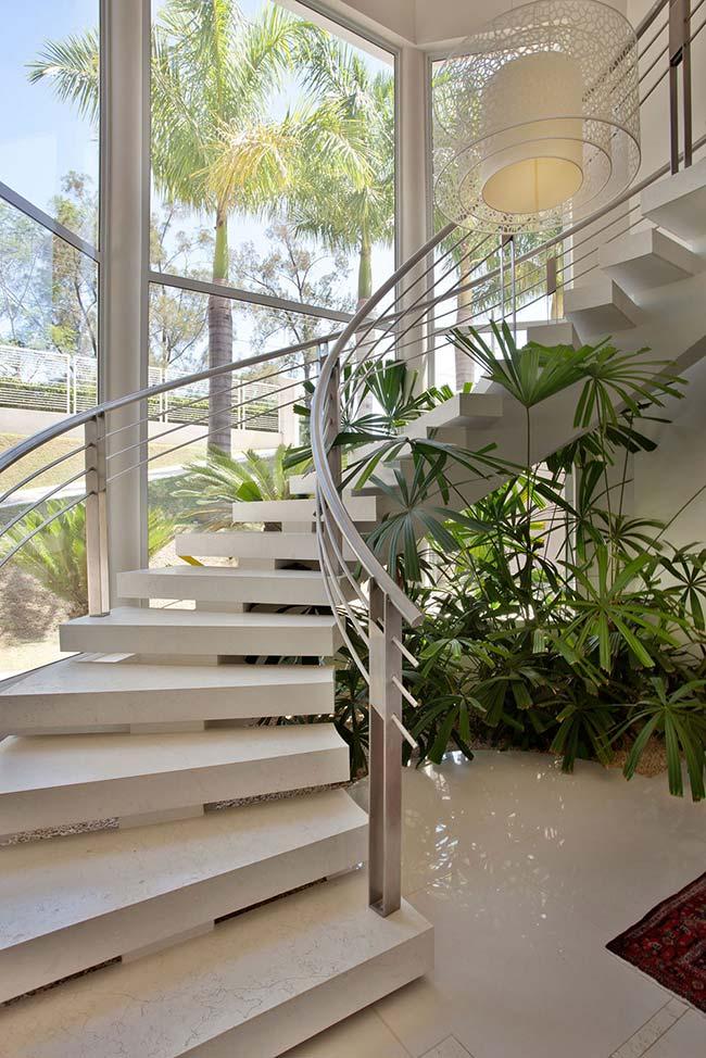 O verde brilhante das palmeiras embaixo da escada faz um belo contraste com a decoração clean do ambiente