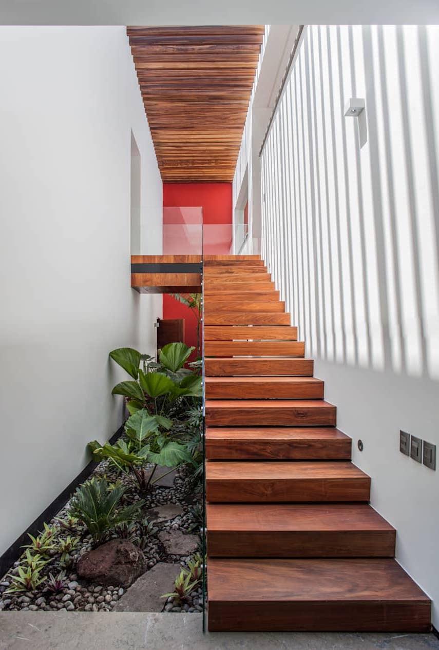 Embaixo dessa escada de madeira foram usadas espécies variadas de plantas e pedras