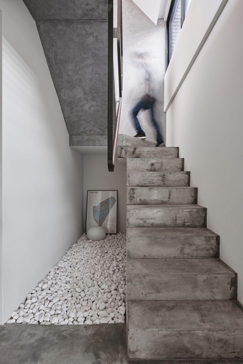 Jardim seco de pedras brancas embaixo da escada de concreto