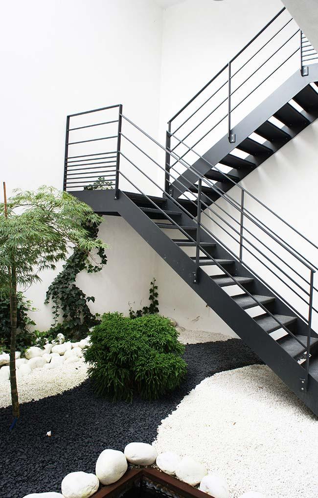 Pedras pretas e brancas desenham o chão do jardim embaixo da escada