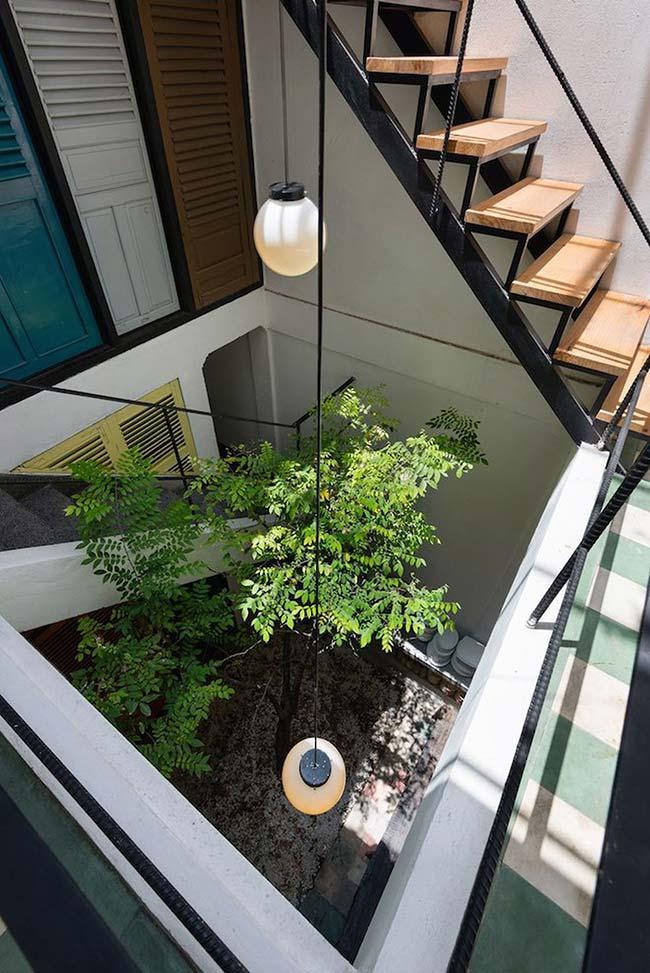 Esse jardim embaixo da escada conta com luminárias próprias