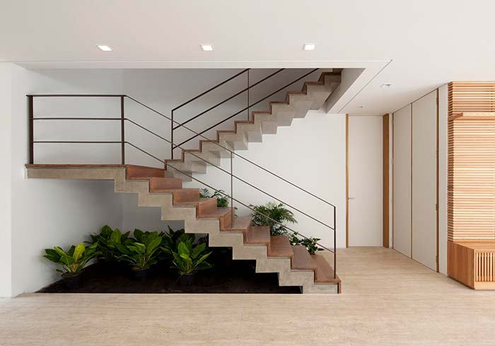 Um jardim embaixo da escada só de vasos