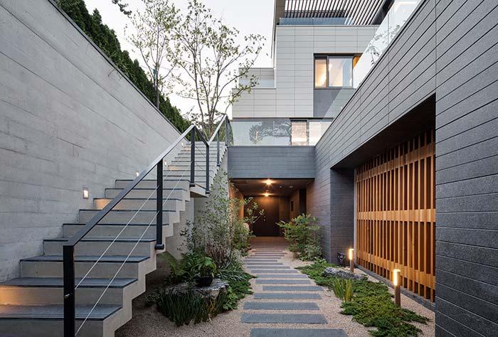 Um jardim que serve tanto para a escada quanto para a entrada da casa