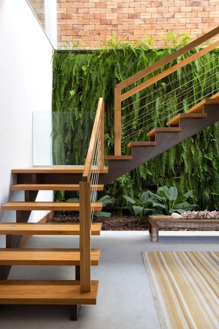 Esse jardim vertical de samambaias não está exatamente embaixo da escada, mas a envolve da mesma forma