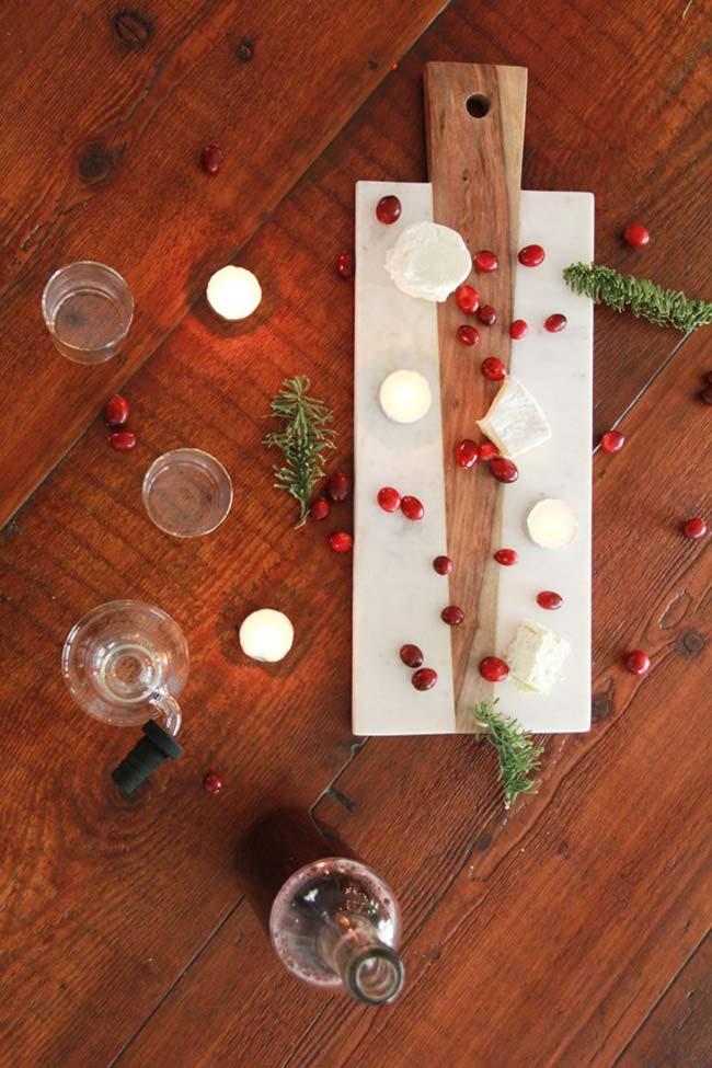 Decoração de mesa de Natal natural com galhos de alecrim, romãs, queijos e velas