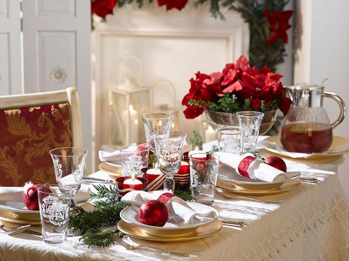 Bolas vermelhas de Natal como decoração até mesmo dos pratos dos convidados