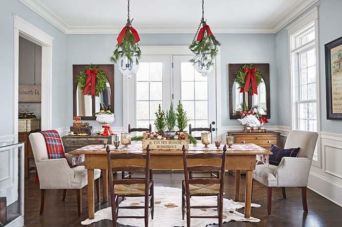 Aqui, a decoração da sala e da mesa é simétrica e toda baseada nos enfeites tradicionais de Natal em verde e vermelho