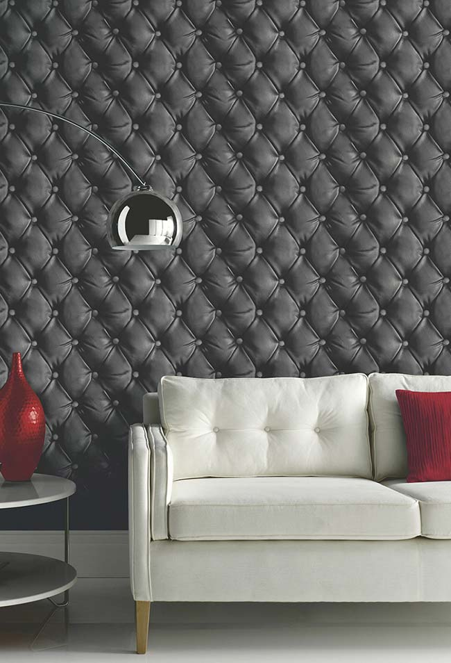 E que tal um estofamento preto para a parede da sala? O papel de parede 3D não para de surpreender