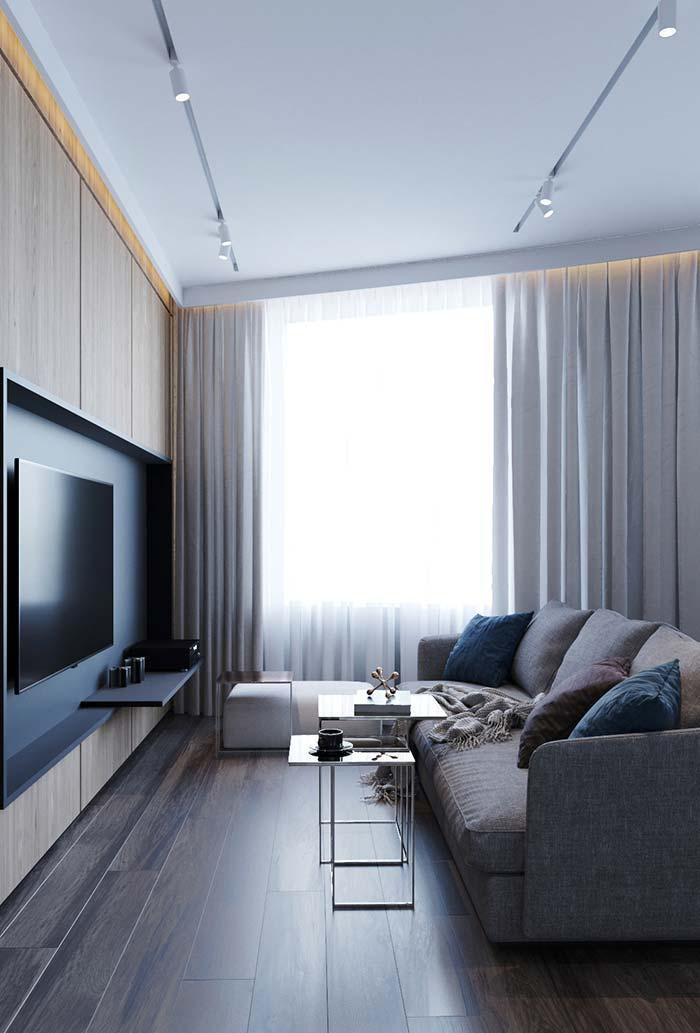 Sala de janela ampla conta com um cortineiro que acompanha toda a extensão da parede