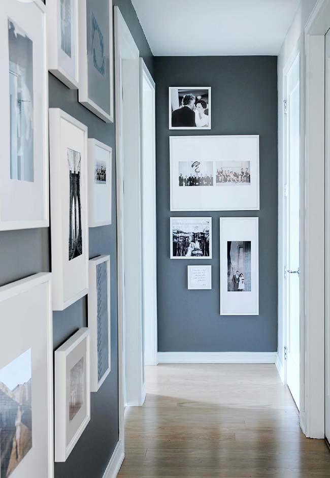 O corredor de tom azul escuro ganhou quadros brancos por toda sua extensão