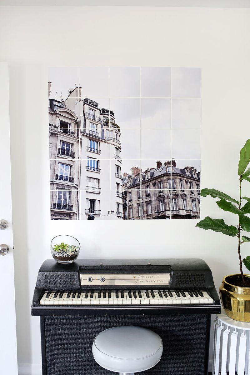 Um quadro com foto de arquitetura histórica decora a parede junto com o piano