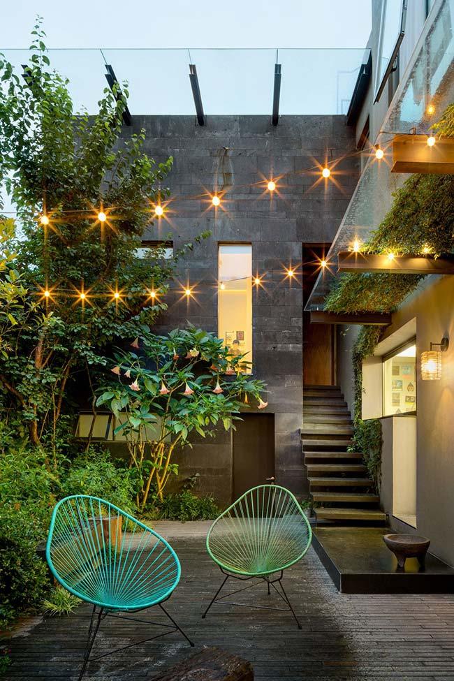 Nesse jardim, as luzes vêm do varal de lâmpadas e da luminária de parede