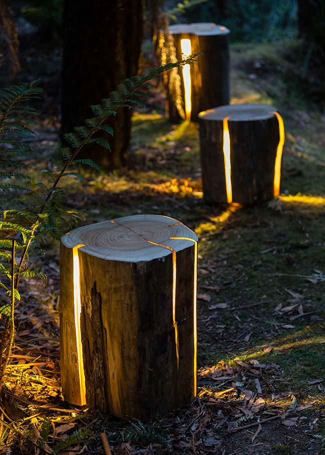 As luminárias naturais, feitas com tronco de árvores, trazem um clima acolhedor e rústico para o jardim