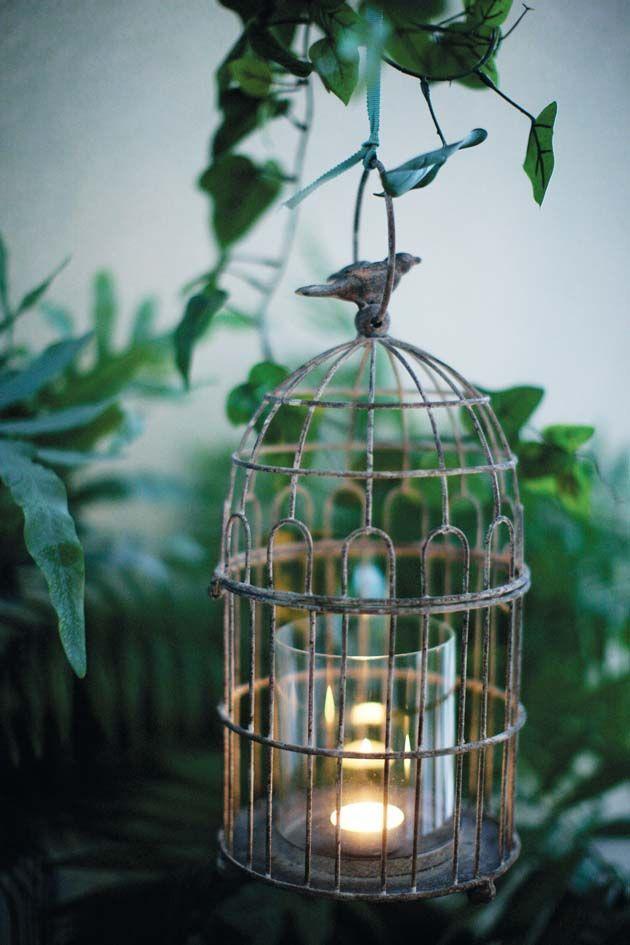 Velas dentro da gaiola iluminam o jardim