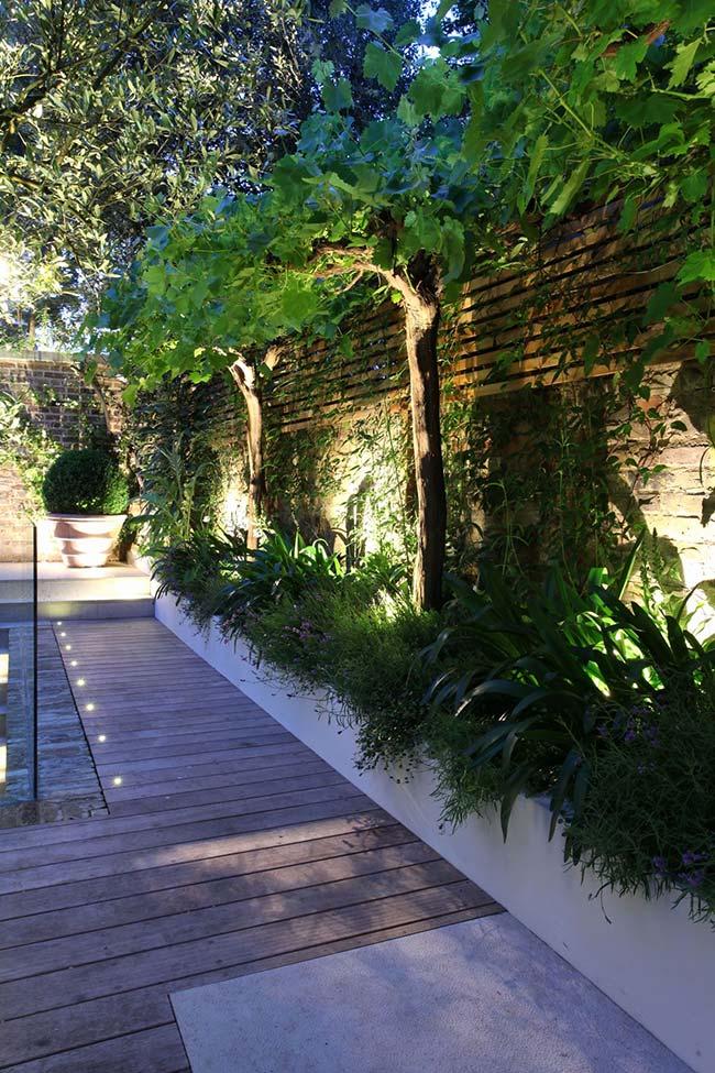 A iluminação desse jardim destaca a vegetação e a parede de tijolos aparentes