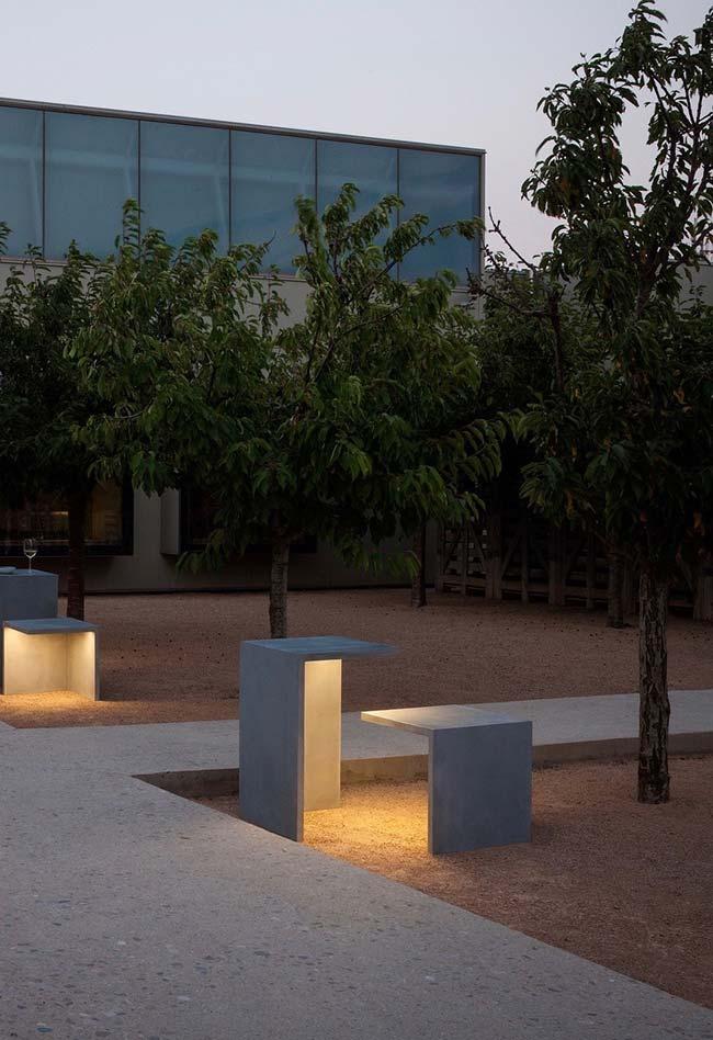 A iluminação desse jardim vem dos bancos e das mesinhas de concreto