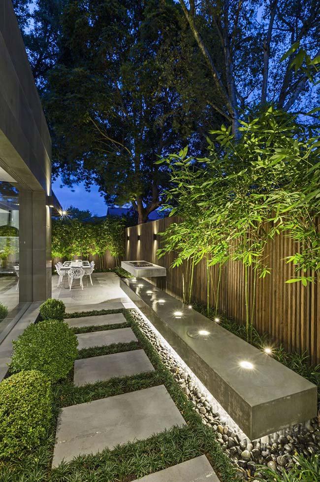 Sobre a faixa de seixos foram instaladas lâmpadas de cor branca que iluminam o chão e destacam os bambus junto ao muro.
