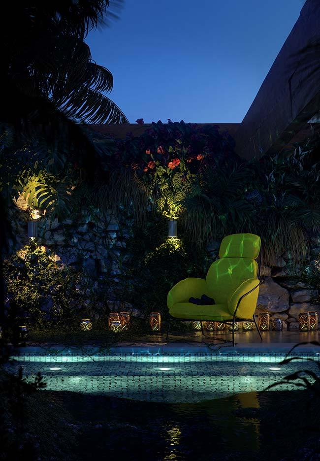 Luz branca destaca o azul da piscina que por sua vez combina com o tom azulado da iluminação na parede