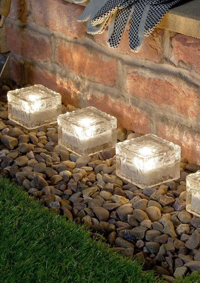 Luminárias de vidro sobre seixos: contraste entre o bruto e o refinado