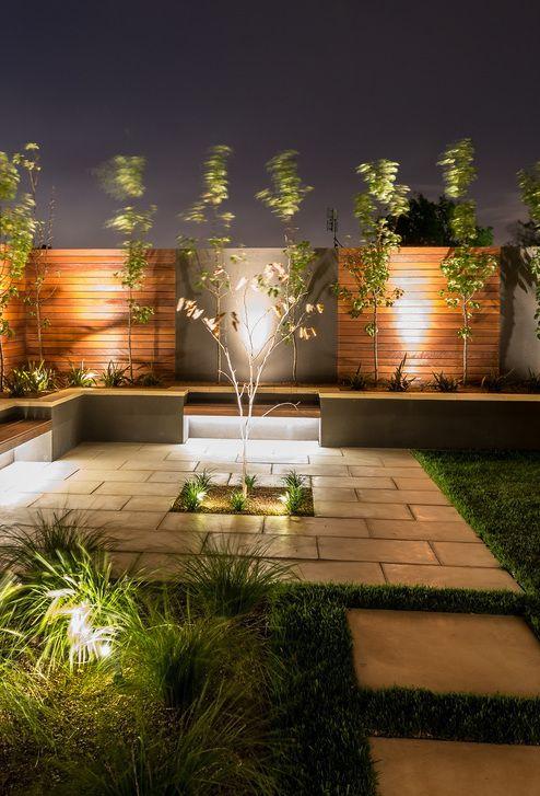 A iluminação do jardim de estilo moderno optou por destacar a parede de madeira