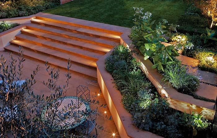 Luzes escondidas entre os arbustos; junto à escada, pontos discretos de luz clareiam o caminho